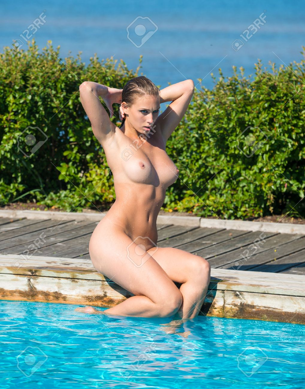 Jeune femme nue à la piscine